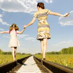 Mother & Daughter walking on railroad tracks